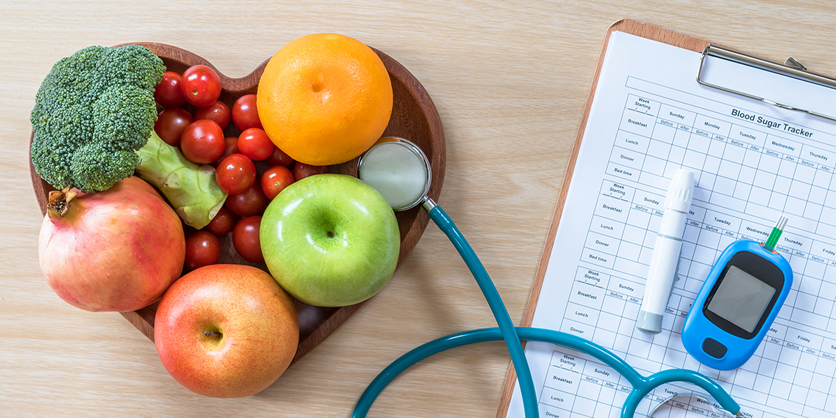 A heart shaped-bowl with colorful fruits and vegetables sits on a table with a stethoscope, glucose monitor, and clipboard.