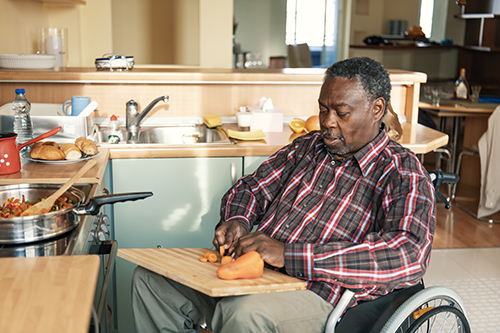 Senior Afro-American in Wheelchairs is Preparing a Lunch at Home