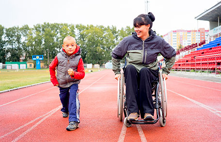 Woman in a wheelchair with a child getting ready to run