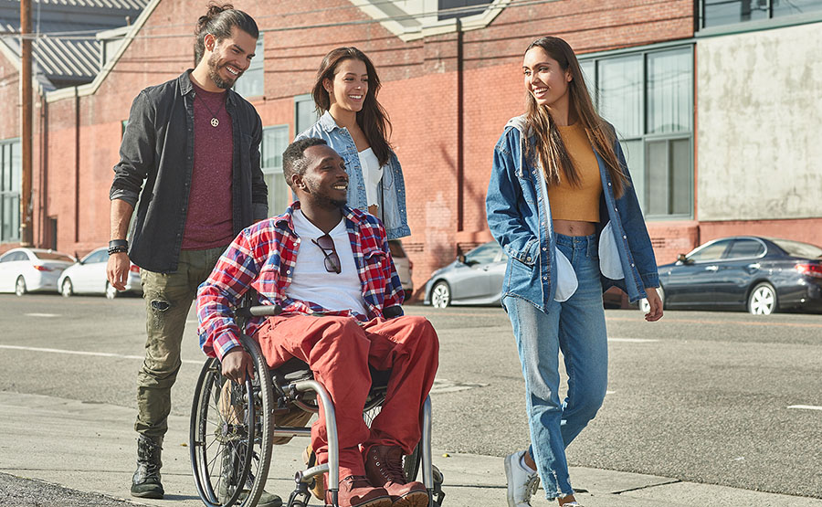 Man in a wheelchair walking with his friends