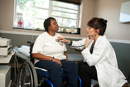 Female doctor examining a female patient who is in a wheelchair