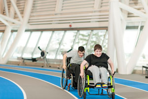 two people in wheelchairs racing on track