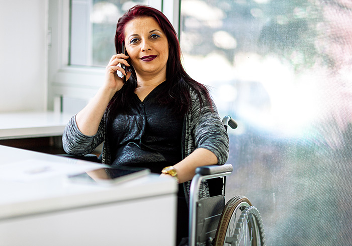 Woman in a wheelchair talking on a cell phone