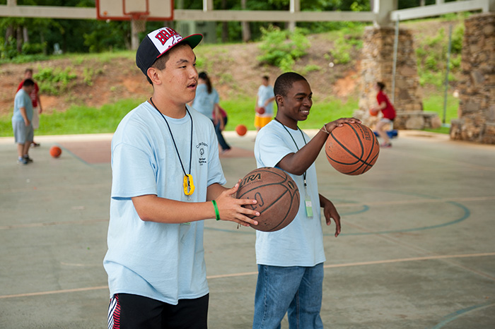 Two boys playing basketball.