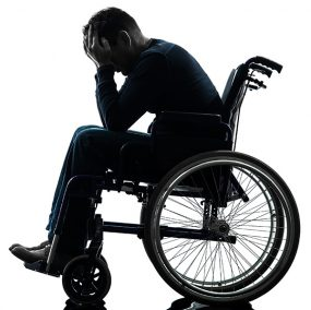 Man sitting in a wheelchair with his head in his hands