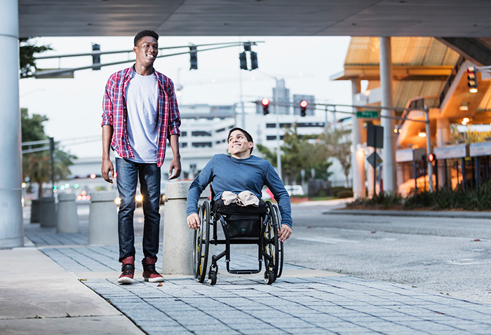 Two men talking while walking down the street. One man is in a wheelchair.