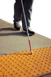 person who is blind with cane walking toward street indicator