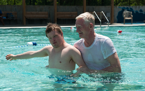 Boy with Down Syndrome in a pool with a man helping him.