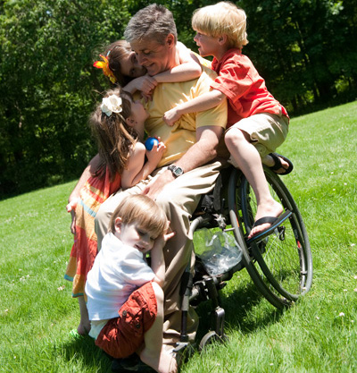 Children hugging their dad in a wheelchair
