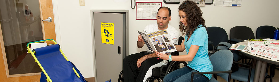 A man in a wheelchair and a woman review emergency plan procedures.