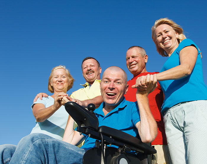 Man in wheelchair with family outside