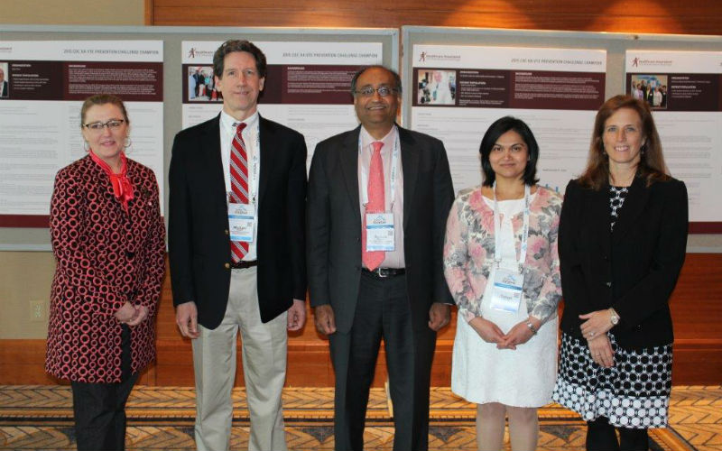 Photo of HA-VTE Prevention Challenge Champions Pose In Front of Posters Showcasing Winning Strategies