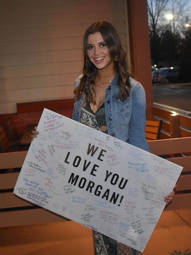 Morgan Spencer holding a We love you Morgan support sign