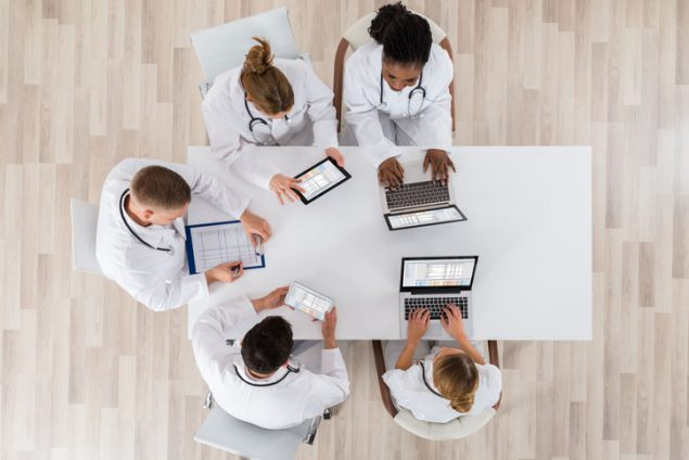Healthcare providers with computers discussing electronic clinical data