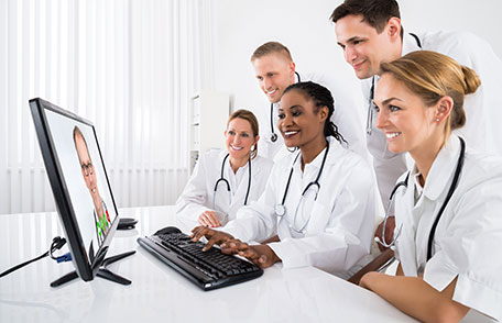 Image of health professionals looking at computer screen.