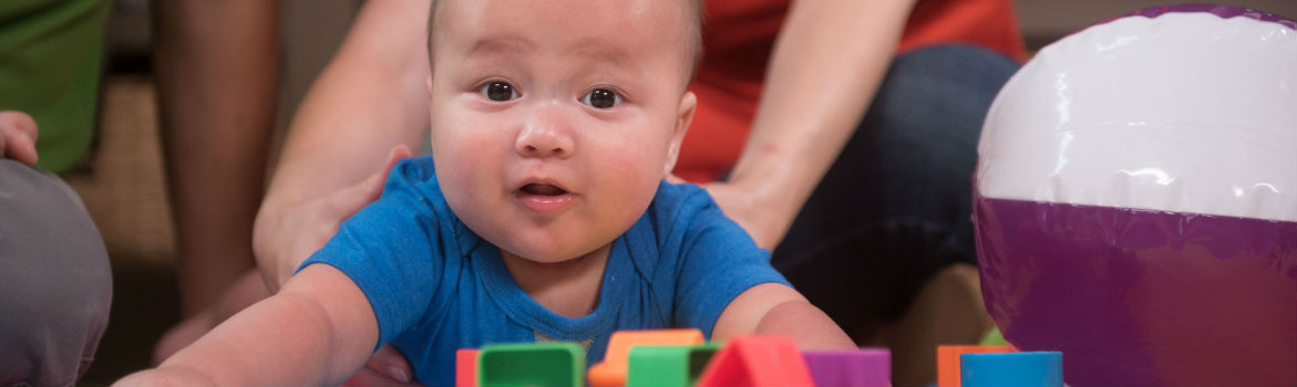 Baby being held up while playing with blocks