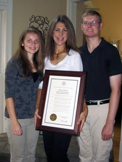 Sasha with his mother, Melissa, and sister, Nadia, holding a proclamation signed by the Governor of Georgia in 2013 declaring September 9 as FASD Awareness Day.