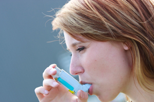 Woman taking asthma medication