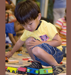 A boy playing with toy trains
