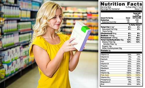 Woman reading nutritional information on a cereal box. Nutrition label highlighting 100% Folic Acid.