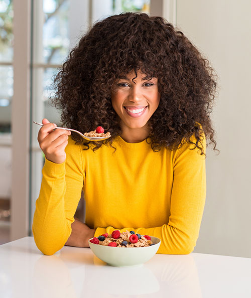 African american woman eating cereals, raspberries and blueberries with a happy face standing and smiling with a confident smile showing teeth