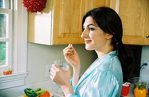 Woman taking folic acid with water.