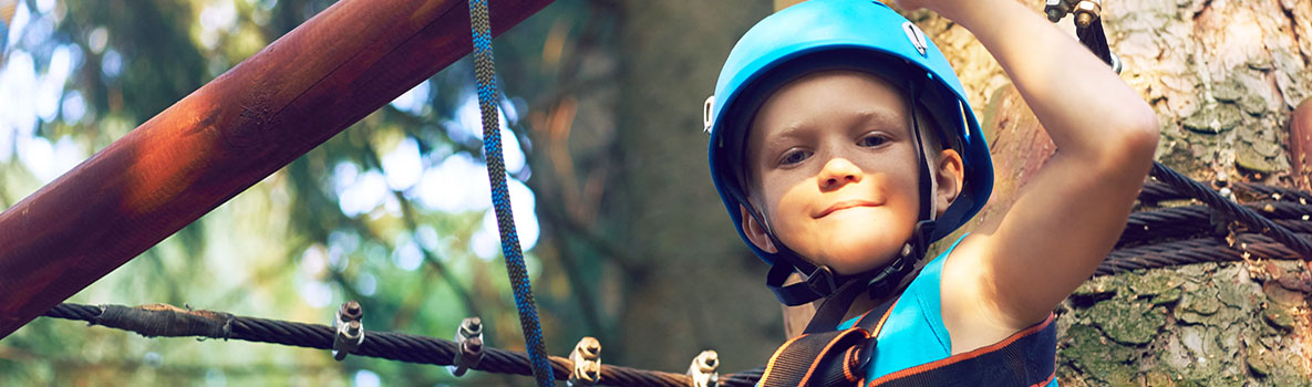 Little boy in a protective helmet and in special equipment passes an obstacle course at height