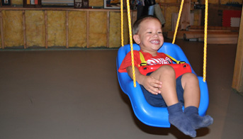 Boy siwning on a swing in the basement