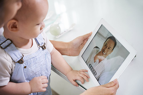 Woman with baby video calling health care provider