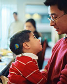Little boy with cochlear implant with his father.