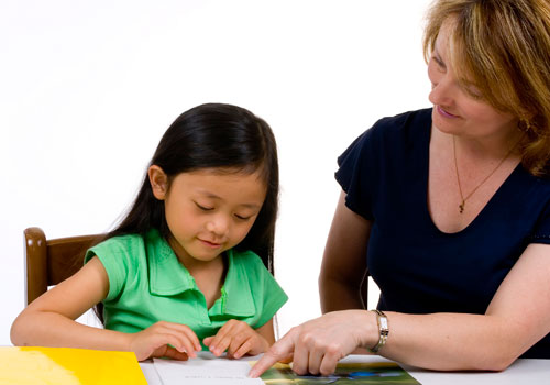A young child sitting at a desk with her teacher