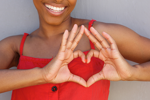 Close up young woman smiling with heart shape hand sign