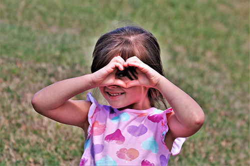 Little girl making a heart gesture with her hands up to her face