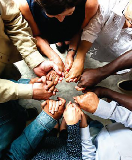 Diverse people holding hands in a circle