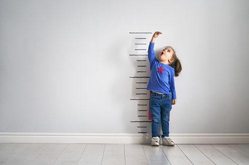 Boy measuring his height on a wall