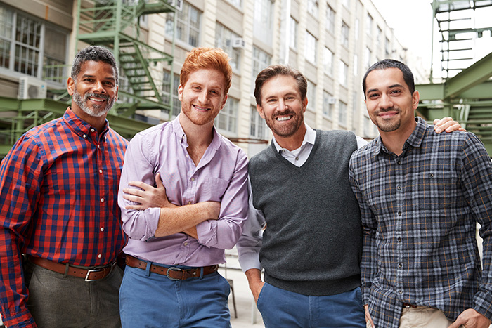 Four male coworkers smiling to camera outside