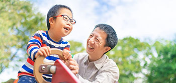 A small child with down syndrome is enjoying with his father at a public park on a sunny day.