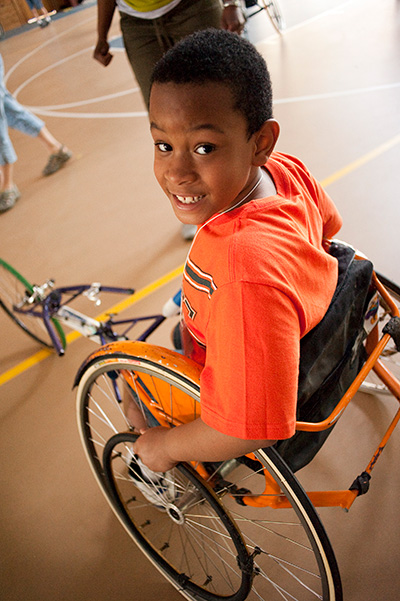 A boy with spina bifida smiles in his wheelchair