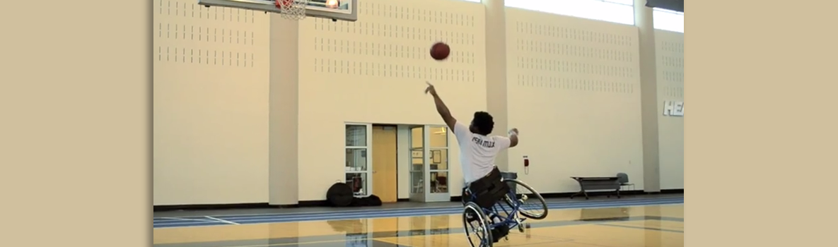 Photo of Rashad shooting a basketball from his wheelchair