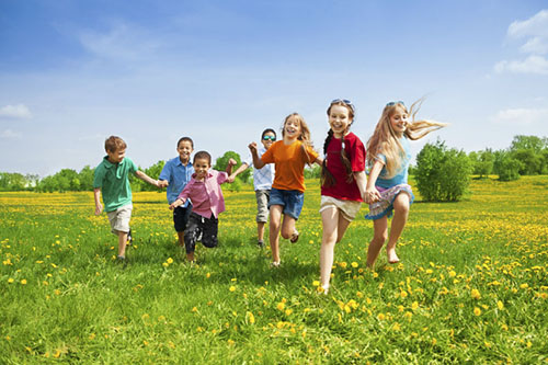 Photo of diverse kids running in grass together.
