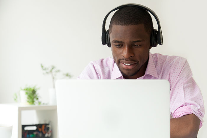 African American man listening to podcast on laptop in office
