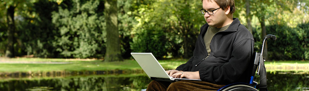 Man in a wheelchair reading his laptop