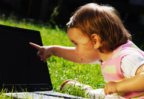 Toddler pointing at a laptop.