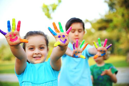 Los niños con caras sonrientes pintadas en sus manos