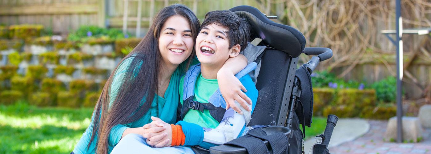 Madre con hijo que está en silla de ruedas.