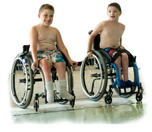 Two boys in wheelchairs getting ready to go in the pool.
