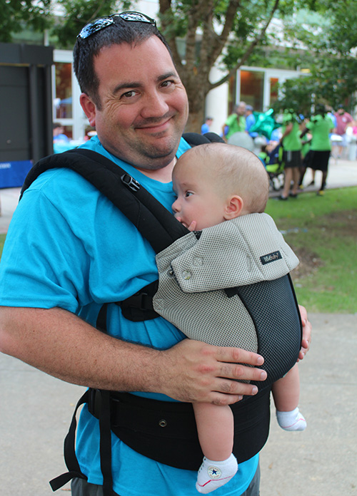 Father holding his baby in a chest baby carrier