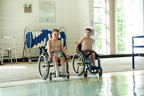 Two boys in wheelchairs at Lakeshore Pool