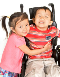 Girl hugging a little boy in a wheel chair.