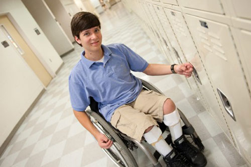 A teen boy with spina bifida at his school locker